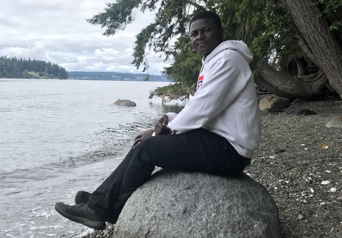 Francis Abugbilla sitting on a rock by water