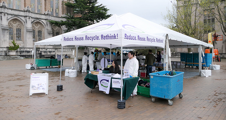 tent with uw recycling text with two people standing in front of it on red square