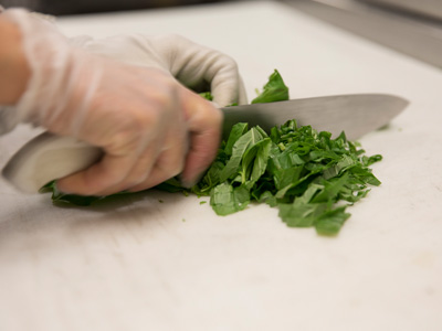 hand with knife chopping fresh greens